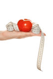 Woman's hand with red tomato and tape measure Royalty Free Stock Photo