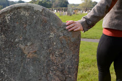 Woman's hand resting on a gravestone Stock Image