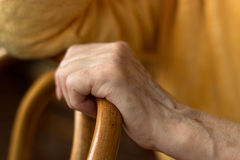 Woman's hand rests on the back of a chair. The hand of an elderly woman in a yellow jacket woman lying on a chair Stock Image