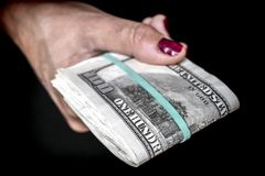 Woman`s hand with several hundred dollar bills. Conceptual image Stock Photography