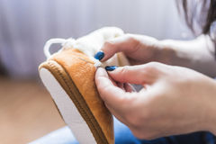 A woman`s hand sews baby plush boots. A woman`s hands are stitched with a needle with white threads children`s light beige plush boots stock photography