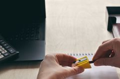 A woman`s hand is sharpen pencil sharpener over the Desk close-up. Study and education concept royalty free stock image