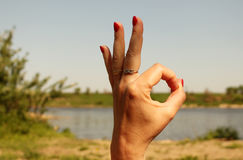Woman`s hand  showing okay sign gesture, against the backdrop of. Woman hand  showing okay sign gesture, against the backdrop of summer lake Royalty Free Stock Images