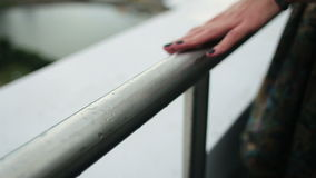 Woman's hand slides over the railing. And going out of focus stock video footage