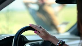 Woman's hand sliding on car's steering wheel stock footage