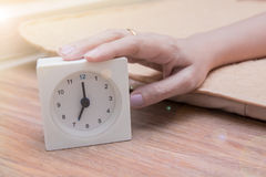 Woman`s hand snoozing white alarm clock in the early morning Stock Photos