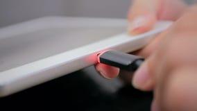 Woman& x27; s-hand som pluggar laddande kabel för svart blixt in i minnestavlan Royaltyfri Bild