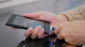 Woman& x27; s-hand som pluggar laddande kabel för svart blixt in i smartphonen Arkivfoto