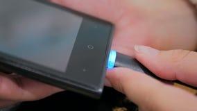 Woman& x27; s-hand som pluggar laddande kabel för svart blixt in i smartphonen Arkivbild