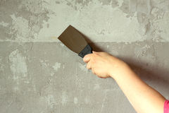 Woman's hand with a spatula plasters concrete wall Royalty Free Stock Photo