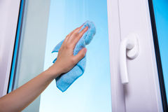 Woman's hand with special rag cleaning window. Close up of woman's hand with special rag cleaning window Royalty Free Stock Photography