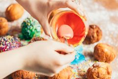 Woman`s hand spooning orange frosting. Out of the glass. Doughnut decorating process Stock Image
