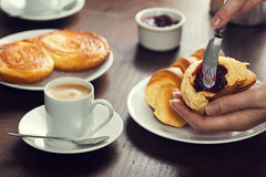 Woman's Hand Spreads Preserves on a Croissant Roll in a Cafe Stock Photos