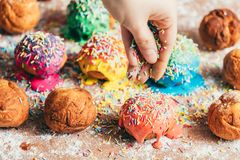Woman sprinkling sugar sprinkles on donuts. Woman`s hand sprinkling sugar sprinkles on colorful donuts. Decoration process stock photo