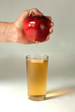 A woman& x27;s hand squeezes fresh juice. Pure apple juice pouring out from fruit into glass. Stock Photos