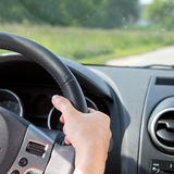 Woman's hand on the steering wheel of a car Stock Images