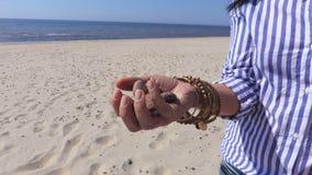 Woman`s hand with stones on beach near sea