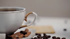 A woman`s hand takes a Cup of coffee close-up. Coffee beans and cinnamon.  stock video footage