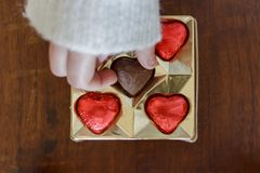 Woman`s hand taking a chocolate heart candy from chocolate box royalty free stock images
