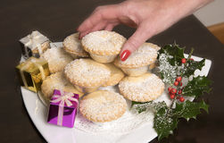 Woman`s hand taking a Mince pie from a plate Royalty Free Stock Photos