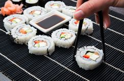 Woman's hand taking philadelphia sushi. Stock Photos
