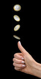 Woman`s hand tosses a coin. Female hand throws a coin in one euro as a lot on a black background Royalty Free Stock Photo