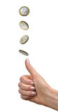 Woman`s hand tosses a coin. Female hand throws a coin in one euro as a lot on a white background Royalty Free Stock Image