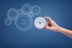 Woman`s hand touching a light-grey metal cogwheel placed against blue background with unfilled cogwheels of various. Shapes and diameters beside. Machines and stock illustration