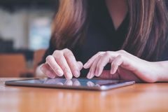 A woman`s hand touching and typing on tablet pc with blur background Stock Photo