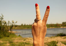 Woman`s hand with two fingers up in the peace or victory symbol. Also the sign for the letter V in sign language. Against the backdrop of summer water Royalty Free Stock Photo