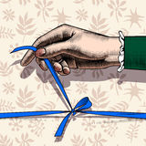 Woman`s hand untying bow of blue ribbon Stock Photos