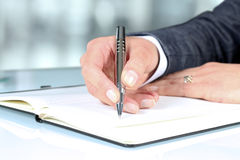 Woman's hand using a pen noting on notepad Royalty Free Stock Images