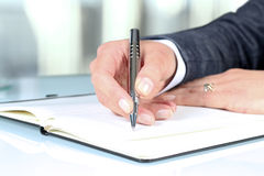 Woman's hand using a pen noting on notepad Royalty Free Stock Photo