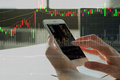 Woman's hand using smart phone. With digital layer of financial graph Royalty Free Stock Images