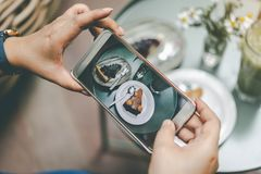 Woman`s hand was photographed cake by her smartphone to get into royalty free stock photos