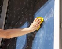 Woman's hand washing a window pane Stock Image