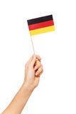 Woman`s hand waving and raising small German flag. Woman`s hand waving and raising small paper German flag, isolated on white Royalty Free Stock Photos