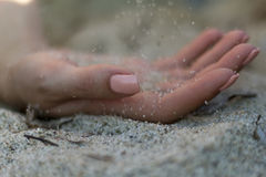 Woman's hand on the white sand. With sand flowing from above. Selective focus royalty free stock photos