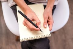 Woman`s hand writing on an blank notebook. stock image