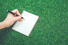 The woman`s hand is writing on a blank notepad with a pen on the Stock Images