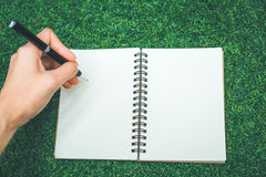 The woman`s hand is writing on a blank notepad with a pen on the Stock Image