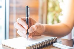Woman`s hand is writing on a blank notepad with a pen on a woode. N desk in office Stock Photography