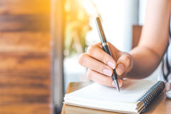 Woman`s hand is writing on a blank notepad with a pen on a woode Royalty Free Stock Photo