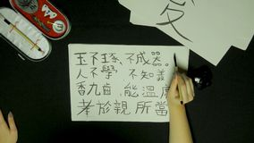 Woman`s hand writing chinese calligraphy. Female hand holding a writing brush Chinese characters.  royalty free stock image