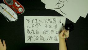 Woman`s hand writing chinese calligraphy. Female hand holding a writing brush Chinese characters.  stock photos