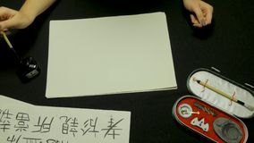 Woman`s hand writing chinese calligraphy. Female hand holding a writing brush Chinese characters.  royalty free stock photo