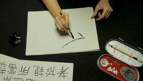 Woman`s hand writing chinese calligraphy. Female hand holding a writing brush Chinese characters.  royalty free stock photos