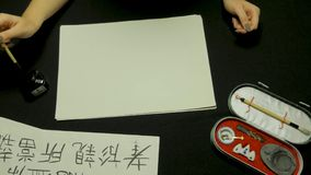 Woman`s hand writing chinese calligraphy. Female hand holding a writing brush Chinese characters Royalty Free Stock Image