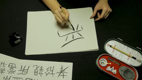 Woman`s hand writing chinese calligraphy. Female hand holding a writing brush Chinese characters Stock Photos