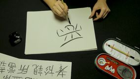 Woman`s hand writing chinese calligraphy. Female hand holding a writing brush Chinese characters Royalty Free Stock Images